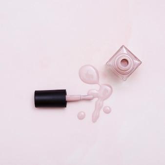 Une bouteille de vernis à ongles rose se répandant sur un fond coloré