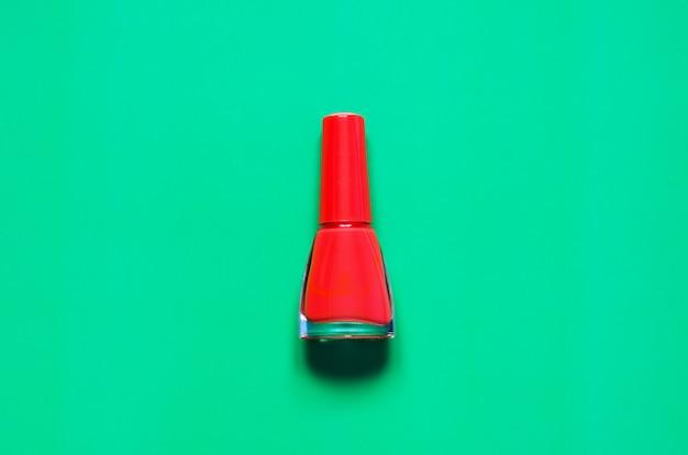 Bouteille de vernis à ongles rouge sur vert