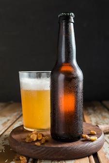 Bouteille en verre de bière avec des noix