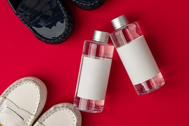Une bouteille en verre blanc de désodorisant est placée le fond est de texture rouge