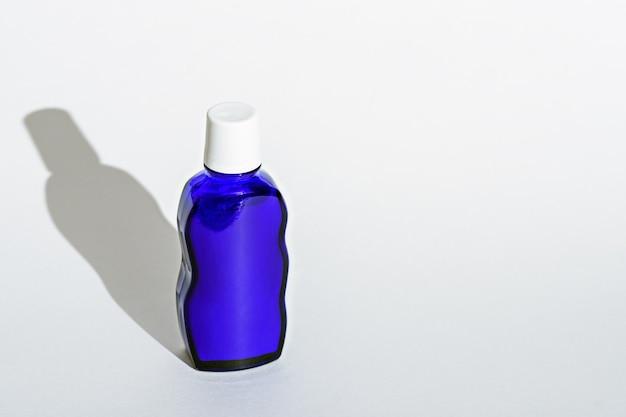 Bouteille en verre bleu classique avec couvercle blanc sur fond blanc avec espace copie