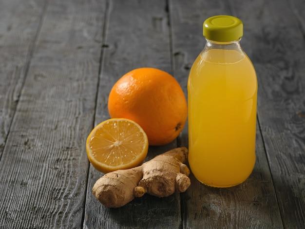 Bouteille en verre avec une boisson de racine de gingembre, citron, orange, miel et cannelle sur une table en bois noire.