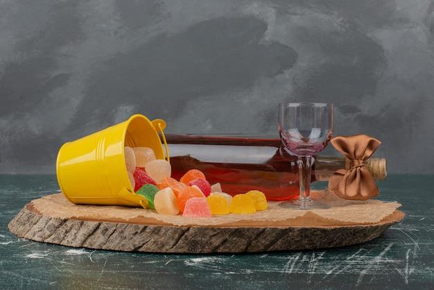 Bouteille avec verre et bonbons à la gelée sur planche de bois