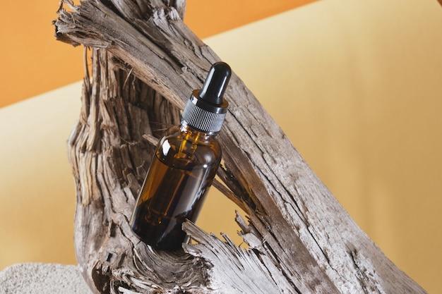 Bouteille en verre brun avec une pipette sur un bois flotté en bois, fond marron, cosmétiques naturels pour les soins de la peau du corps, sérum ou huile contre le vieillissement cutané