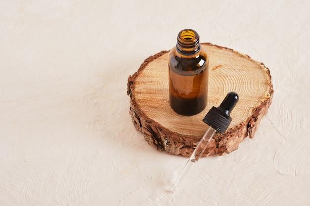 Bouteille en verre brun avec une pipette sur une coupe de scie d'un arbre sur un fond texturé beige