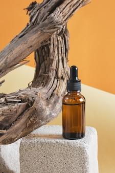 Bouteille en verre brun avec une pipette sur un podium en béton sur fond de bois flotté, fond brun espace copie concept cosmétique naturel