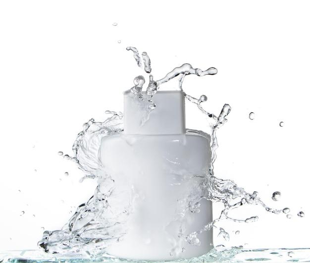 Bouteille en verre carré blanc sur fond blanc et éclaboussures d'eau
