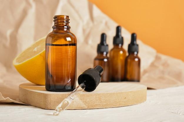 Bouteille en verre citron et marron avec compte-gouttes pour sérum ou huile cosmétique sur un podium en bois en forme de cœur, concept de soins corporels respectueux de l'environnement