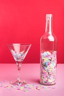Bouteille et verre avec des confettis colorés