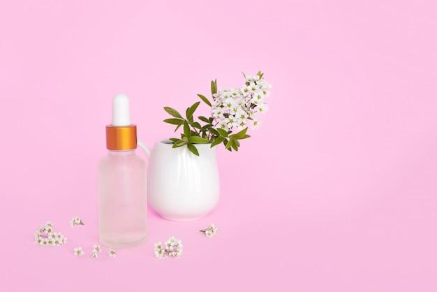 Bouteille en verre cosmétique avec de l'huile. contenant pour un produit pour femme avec de petites fleurs blanches sur fond turquoise. pot cosmétique. place pour le texte