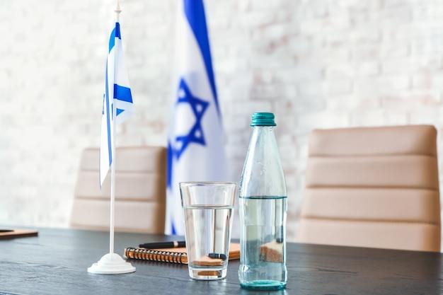 Bouteille et verre avec de l'eau et drapeau d'israël sur table dans le bureau de l'ambassade
