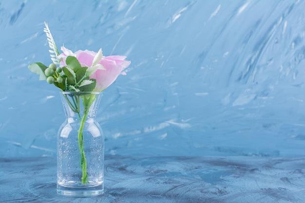 Bouteille en verre de fleur rose simple avec des feuilles sur bleu.