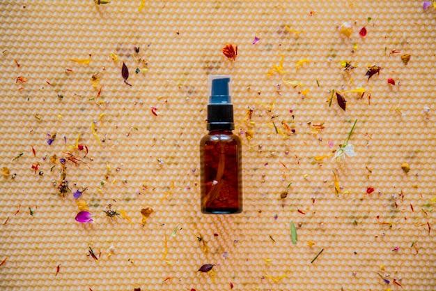 Bouteille en verre avec des fleurs sèches sur nid d'abeille. vue ci-dessus