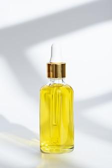Bouteille en verre gros plan avec pipette avec de l'huile cosmétique jaune sur fond blanc
