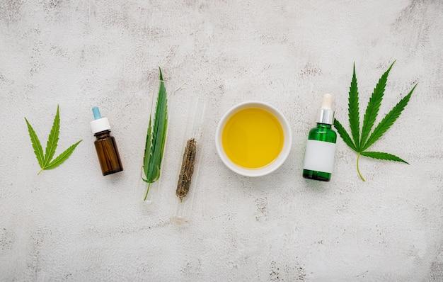Bouteille en verre d'huile de cannabis et de feuilles de chanvre posées sur du béton.