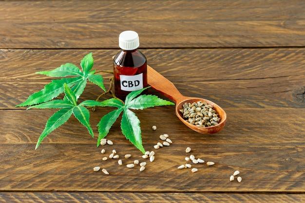 Bouteille en verre avec huile de cbd, teinture de thc et feuilles de chanvre sur une table en bois.