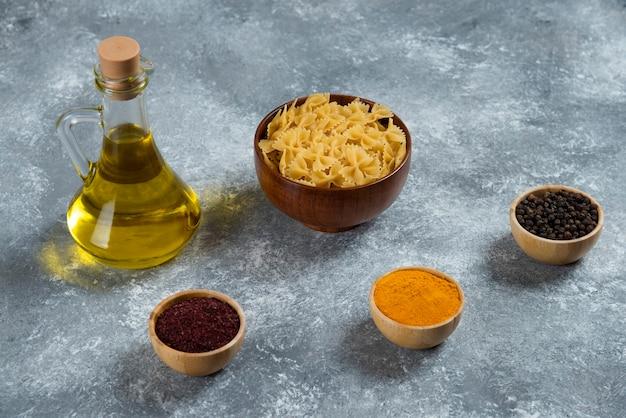 Une bouteille en verre d'huile avec des macaronis crus.