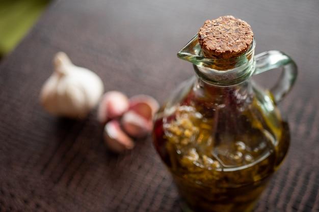 Bouteille en verre d'huile d'olive extra vierge et ails dans une table sombre.