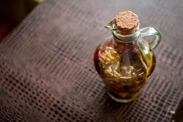 Bouteille en verre d'huile d'olive extra vierge dans une table sombre.