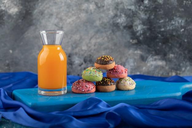 Une bouteille en verre de jus avec des beignets colorés.