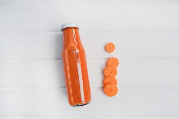 Bouteille en verre de jus de carotte bio et carotte fraîche