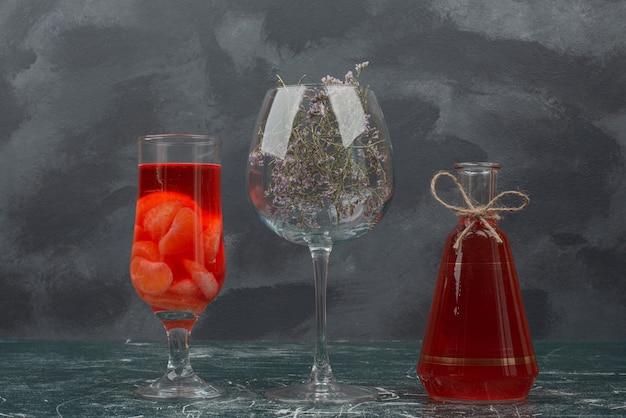 Bouteille et verre avec jus et verre avec fleur.