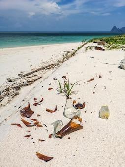 Bouteille en verre, ordures en plastique, mousse et déchets sales sur la plage en été.