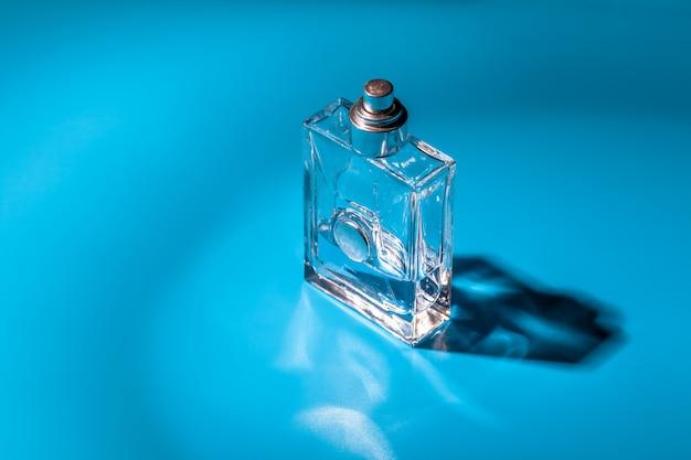 Bouteille en verre de parfum sur bleu clair. eau de toilette