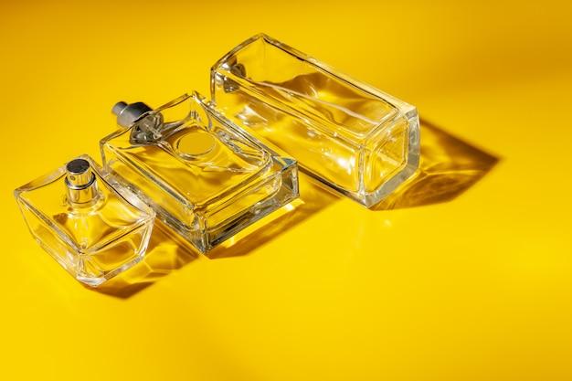 Bouteille en verre de parfum sur fond jaune clair. eau de toilette
