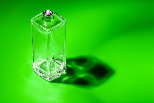 Bouteille en verre de parfum sur vert clair. eau de toilette