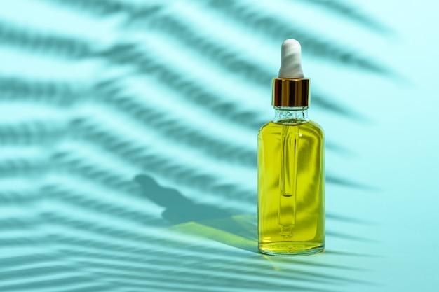Bouteille en verre avec pipette avec de l'huile cosmétique jaune sur fond bleu avec ombre, espace copie
