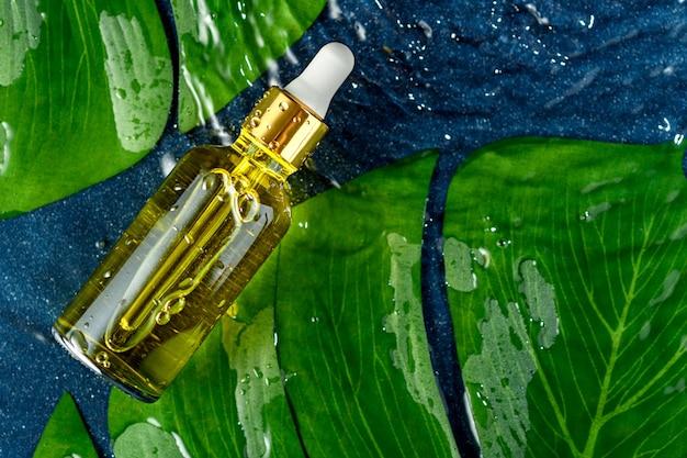 Bouteille en verre avec pipette et sérum jaune cosmétique sur les feuilles vertes et l'eau, concept de soins de la peau