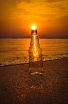 Bouteille en verre sur le sable au coucher du soleil