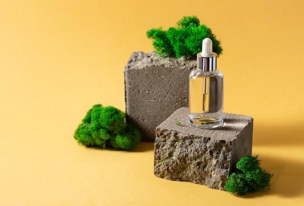 Bouteille en verre avec sérum cosmétique sur podium en brique avec de la mousse