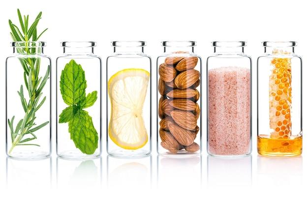 La bouteille en verre de soins de la peau et de gommages corporels faits maison avec des ingrédients naturels isolés sur fond blanc.