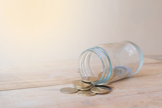 Une bouteille en verre tombant sur un tas de pièces et sur une table en bois - concept d'investissement, d'affaires, de finance et bancaire