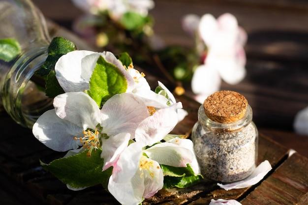 Bouteille en verre transparent avec de l'eau et des fleurs de pommier sur une table en bois rustique avec un petit pot de sable de mer. fond sombre