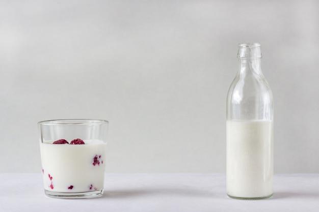 Bouteille en verre et verre de yaourt aux framboises.