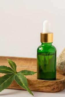 Bouteille en verre vert avec de l'huile de cbd, de la teinture de thc et des feuilles de chanvre sur une surface blanche