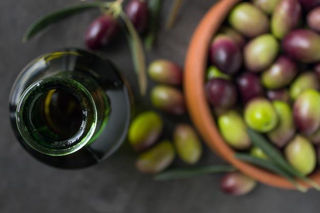 Bouteille de verre vert avec de l'huile d'olive à côté des olives mûres