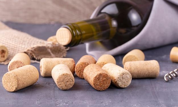 La bouteille de verre de vin blanc avec des bouchons en liège sur fond de table en bois