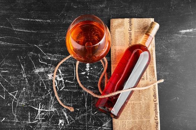 Une bouteille et un verre de vin rosé sur un journal vintage.