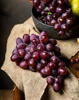 Bouteille et verre de vin rouge, raisin et liège sur chaise. melon, morceau de melon. raisin rose, poire. nature morte de nourriture. photographie d'aliments sombres. concept d'automne. alcool, viticulture.