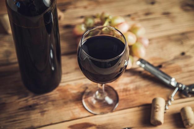 Bouteille et verre de vin rouge avec des raisins mûrs