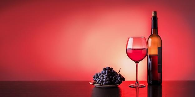 Bouteille et verre de vin rouge avec des raisins sur une table sombre en bois avec espace de copie. bannière.