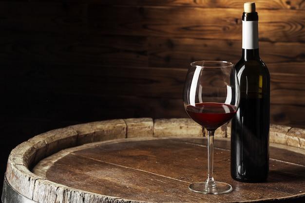 Bouteille et verre de vin rouge sur un tonneau en bois tourné avec un fond en bois foncé