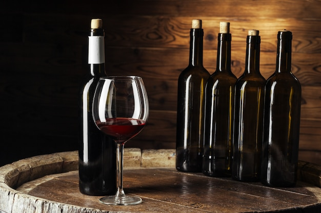 Bouteille et verre de vin rouge sur un tonneau en bois