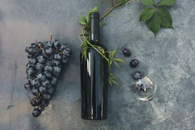Bouteille de verre à vin de vigne verte de vin rouge et de raisin mûr sur le dessus de fond de table en pierre sombre vintage vi...