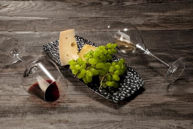 Une bouteille et des verres de vin rouge et blanc avec des fruits