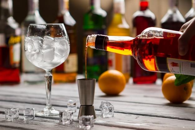 La bouteille verse le liquide dans le jigger. glaçons dans un verre à vin. vin sec pour un cocktail savoureux. ingrédient clé pour les boissons alcoolisées.